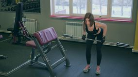 The athlete lifts the bar in a semi-bent position for the development of muscles stock video footage