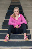 Athlete looking down the steps. Attractive blond sitting on concrete steps looking ahead stock photo