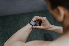 Athlete looking at his smartwatch fitness app after workout royalty free stock photos