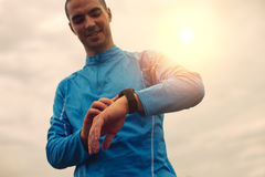 Athlete is looking at smart watch. Sunlight effect Stock Photos