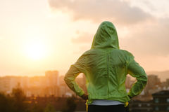 Athlete looking sunset over city skyline after exercising. Back view of athlete looking sunset over city skyline after exercising. Motivation, sport and fitness Stock Images
