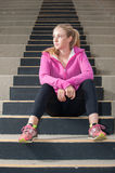 Athlete looking to the light. Attractive blond sitting on concrete steps looking to left royalty free stock photo