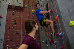 Athlete looking at trainer climbing wall at gym Stock Images
