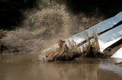 Athlete makes a splash. An Athlete participating in the 2014 mudathlon, makes a big splash into muddy water at this messy sport event Stock Photography