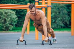 Athlete male at the city park making some push up Stock Images
