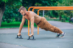 Athlete male at the city park making some push up Royalty Free Stock Image
