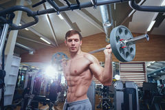 Athlete male doing exercises with a bar lying down in the gym.  Royalty Free Stock Photos