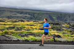 Athlete male runner running on mountain road. Running man jogging fast training cardio for marathon on countryside path in nature landscape, volcano background Stock Image