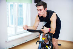 Athlete man biking in the gym, exercising his legs doing cardio training cycling bikes Royalty Free Stock Images