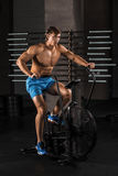 Athlete man biking in the gym. Athlete man biking in the gym, exercising his legs doing cardio training cycling bikes Royalty Free Stock Photos