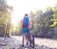 Athlete man crossing mountain river with bicycle Stock Photography