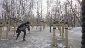 Athlete man doing crossfit exercise with expander on outdoor winter training. Athlete man doing crossfit exercise with expander on outdoor training in winter stock video