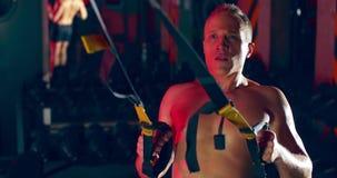 Athlete man doing pull-ups on trx cables in sports gym `premium gym`. Ukraine Lviv 15.03.2020