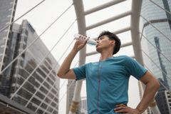 Athlete man drink water after jogging in town. Asian athlete man with red earphone drinking bottle of water after jogging or running in modern Bangkok city Royalty Free Stock Photography