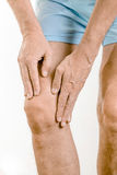 Athlete man feeling pain to the knee and to the quadriceps. Athlete man massaging a painful quadriceps and the knee after a sport accident. It could be a stock photos