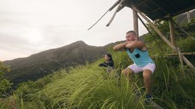 Athlete man and fit woman training squat exercise on tropical mountain background. Sport couple squatting while training.  stock footage