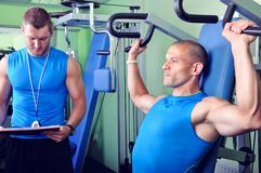 Athlete man in gym with personal fitness trainer. Athlete men with personal fitness trainer Royalty Free Stock Photo