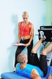 Athlete man in gym with personal fitness trainer Royalty Free Stock Image