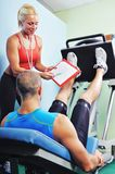 Athlete man in gym with personal fitness trainer Stock Photo