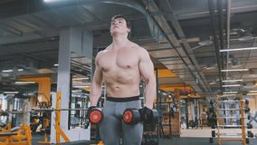 Athlete man lifting dumbbells without shirt in the gym. Close up Stock Photo