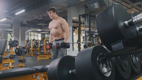 Athlete man lifting dumbbells without shirt in the gym. Close up Royalty Free Stock Photography