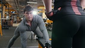 Athlete man lifting dumbbells - training in the gym, attractive girl looks at him. Close up stock video