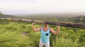 Athlete man lifting heavy wooden bar on tropical hill and highlands landscape. Bodybuilder training press exercise with.  stock video footage