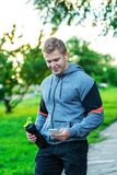Athlete man listening to music on headphones. Writes a message in the smartphone. Holds a bottle of water with protein. Happy smiling. Lifestyle athlete Royalty Free Stock Image