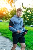 Athlete man listening to music on headphones. Writes a message in the smartphone, social networks. Holds a bottle of. Athlete man listening to music on Stock Images