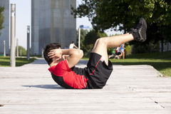 Athlete man making abdominals Stock Photos