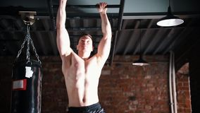 An athlete man moving forward on his hands using a ceiling ladder. Mid shot stock video