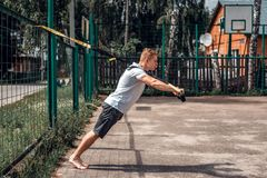 Athlete, a man in open air, plays sports, in summer in city, in shorts with a white shirt, squeezes out on simulator Royalty Free Stock Image