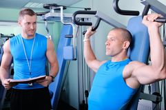 Athlete man with personal fitness trainer. Athlete men in gym with personal fitness trainer Royalty Free Stock Images