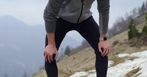 Athlete man runner warming up or cooling down stretching.Real people adult trail running sport training in autumn or. Winter in wild mountain outdoors nature stock video footage