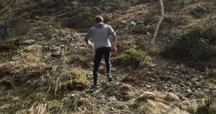 Athlete man running through snowy path.Climbing side.Real people adult trail runner sport training in autumn or winter. In wild mountain outdoors nature, bad stock footage