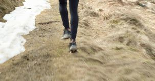 Athlete man running through snowy path.Following behind legs detail.Real people adult trail runner sport training in stock video