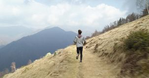 Athlete man running through snowy path.Following behind.Real people adult trail runner sport training in autumn or. Winter in wild mountain outdoors nature, bad stock video