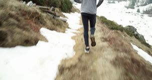 Athlete man running through snowy path.Following behind.Real people adult trail runner sport training in autumn or. Winter in wild mountain outdoors nature, bad stock footage