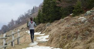 Athlete man running through snowy path.Following behind.Real people adult trail runner sport training in autumn or. Winter in wild mountain outdoors nature, bad stock video footage