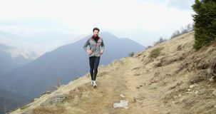 Athlete man running through snowy path.Following front.Real people adult trail runner sport training in autumn or winter. In wild mountain outdoors nature, bad stock video