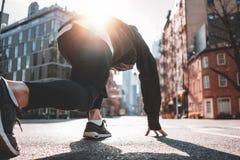 Male runner preparing to run straight through New-York streets. Athlete man in running start pose on urban street. Male runner preparing to run straight through royalty free stock photo