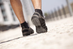 Athlete man shoes walking. Athlete man shoes running in the city (selective focus Stock Photos