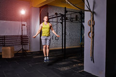 Athlete man in the sportwear using jump ropes for the workout in a cross-training gym. Sportsman in the t-shirt, shorts and sportive shoes. Healthy lifestyle Royalty Free Stock Photo