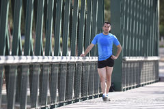 Athlete man stretching legs warming up calf muscles before running workout leaning on railing city urban park Royalty Free Stock Photo