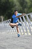Athlete man stretching legs warming up muscles before running workout leaning on railing city urban park Stock Photo