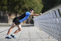 Athlete man stretching and warming up muscles before running workout leaning on railing city urban park Stock Photo