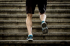 Athlete man with strong leg muscles training and running urban city staircase in sport fitness and healthy lifestyle concept. Young athletic legs of runner sport Royalty Free Stock Photography