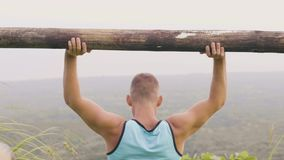 Athlete man training press exercise with wooden barbell on green mountain valley. Fitness man using timber bar for stock footage