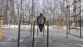Athlete man training push ups exercise on bar on winter sport ground stock images