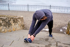 Athlete man warming up before running. Sport life spring winter Stock Image